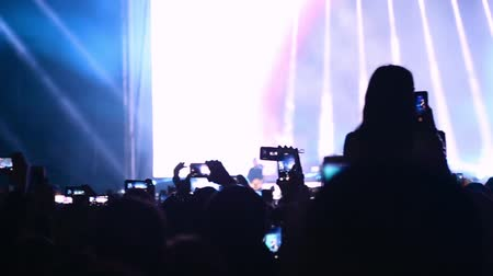 szemléltető : Phones in the hands of a crowd of viewers take videos and photos at a music festival. People taking video and photos on mobile smart phone at concert party crowd. A group of fans with phones. Stock mozgókép