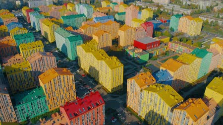 townhouse : Infrastructure of a modern residential area with colorful houses. A modern residential complex with schools and kindergartens in the same style. Camera moves back. Aerial view, drone video footage.