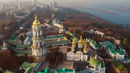 territory : Bell tower Kiev Pechersk Monastery on Dnieper shore from drone above. Aerial view architecture Kiev Pechersky Monastery. Kyiv-Pechersk Lavra on a hill on the banks of Dnipro river. Aerial view video. Stock Footage