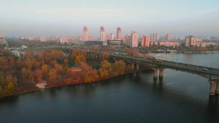 roadtrip : Flying back over the bridge across the wide Dnieper River, Kiev, Ukraine. Cars move on a road bridge over a river. Modern city and autumn yellow trees on a background at sunset. Autumn time. Stock Footage