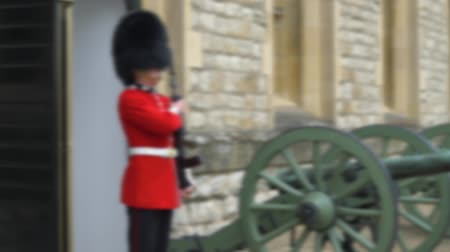 охранять : Blurred video footage. Traditional march of the British guard at the combat post. Queens Guard is the contingents of infantry and cavalry soldiers charged with guarding official royal residences.