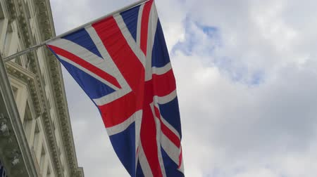 brexit : British flag close-up on a flagpole against a blue sky. Flag Day in Britain. British flag on a historic building in London. England flag waving on the top Stock Footage