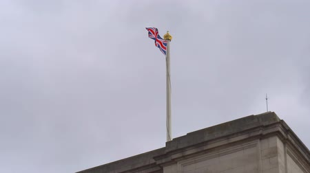 buckingham palace : Flag pole with krown and British flag Union Jack in Buckingham Palace. England flag waving on the top. Union flag on a pole flying against a cloudy sky. Union Jack. British flag waving in bad weather. Stock Footage