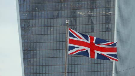 great video : British flag Union Jack on the background of walkie-talkie skyscraper in London. British flag waving in the wind, close up. England flag waving on the top in London City. Slow motion, video footage. Stock Footage