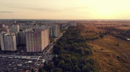 Outskirts of a big city, aerial view. Forest plantation on the outskirts of the big city. Large multi-storey building on the outskirts of city. View from aerial above. Warm toning, summer evening city