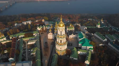 territory : Flyby around Kiev Pechersk Lavra, Ukraine. Aerial view at sunset of the Kiev-Pechersk Lavra - one of the main symbol of Kiev, Ukraine. View to river Dnipro. Top down view, drone video footage. Stock Footage