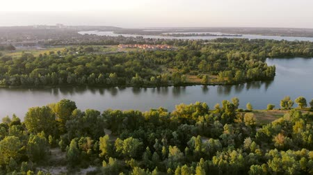 пригород : Country houses near the big river, view from above at sunset. Slow rising aerial establishing shot of a sunset over cottage town. Aerial footage of a Ukrainian countryside village with small houses.