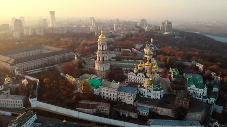 territory : Flyby around the monastery. Archutecture Kiev Pechersk Lavra on evening city landscape. Aerial view Kiev Pechersky Monastery in Ukraine. Ancient Christian architecture in modern Kiev city.