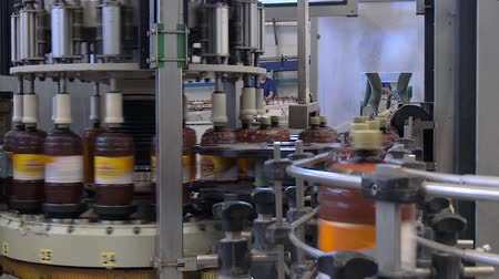 klasa : Worker at brewery near a conveyor belt monitors product quality. Conveyor with beer filled in bottles is at the brewery. Shop for bottling beer in a brewery with workers. Beer in brown plastic bottles