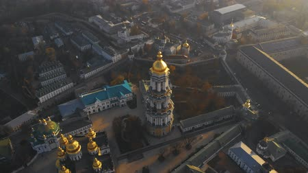 territory : Bell tower Kiev Pechersk Lavra on evening city landscape. Aerial view architecture Kiev Pechersky Lavra in evening sunlight. Ancient orthodox architecture in Kiev city, Ukraine. Top down aerial view. Stock Footage