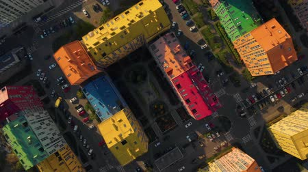construtor : Camera slowly rotates and take off over a modern residential complex with colorful houses similar to a constructor on a bright sunny day. Cars are parked in the courtyard of the house. Top down view.