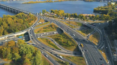 мостовая : Road junction with heavy traffic, autumn time. Aerial view footage of traffic two-level junction, moving cars by intersection of roads, bridges. Urban city.