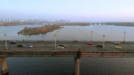 мостовая : Cars ride across the river on a road bridge. View from the drone flying near the bridge. In the background a city landscape in autumn time. Стоковые видеозаписи