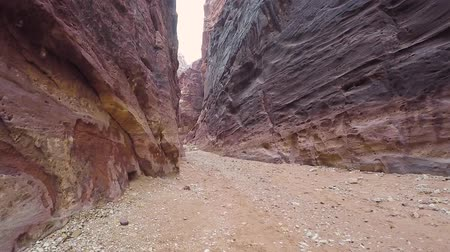 резной : Camera moves in Al Siq canyon, which goes to the ancient city of Petra. Walking inside the Al Siq Canyon towards the Treasury in Ancient City of Petra. Petra is archaeological city in southern Jordan.