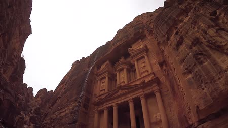 estreito : Treasury Facade Carved Out of a Red Rock Sandstone In Ancient City of Petra. View of the City of Petra. Petra View of the City From the Bottom Up. Beautiful Historic Building. Wide angle video