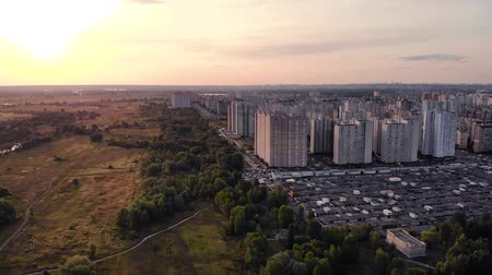 külvárosok : Evening city aerial view. Drone flies over the evening city in the sunset light. Tall houses on outskirts of the city near a forest plantation. Large multi-storey building on outskirts of the city.