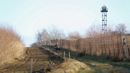 border crossing : Border guards on ATV make inspection border in the winter season. Two border guards ATV. State border with a fence and plowed land. Stock Footage