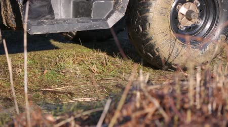 tüm : Riding a quad bike in the mud. The wheels of the ATV slowly drive through the ground. The ATV goes off-road, close-up. Wheels in the mud on a dirt road. Off-road driving. ATV off road wheels Stok Video