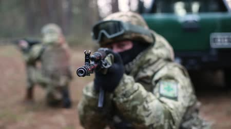 squad car : Soldiers team holding machine gun forward to attack enemy. Against a blurred background with cars and soldiers. Armed military man soldier shooting a gun. Machine gun barrel look at camera.