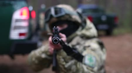 フォロー : Soldier is tracking a target. Soldier aims from a machine gun directly at the camera. Against a blurred background with cars and soldiers. Armed military man soldier shooting a machine gun. 動画素材