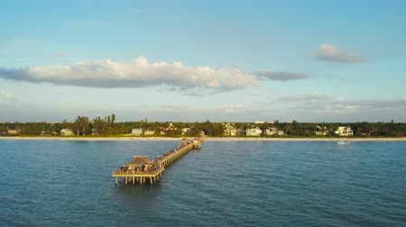 neapol : Pier in Naples by Aerial Drone. Naples Beach and Fishing Pier at Sunset, Florida. Drone flies around a fishing pier in Naples, Florida USA. Aerial orbit Naples Beach Pier. Aerial view video.