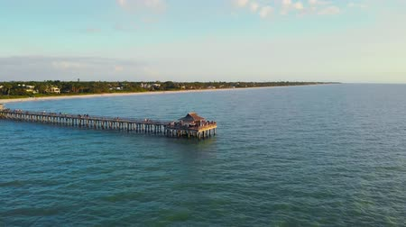 napoli : Naples Beach and Fishing Pier at Sunset, Florida. Drone flies around a fishing pier in Naples, Florida USA. Drone flies forward low above the water at sunset. View from ocean to the pier with tourists