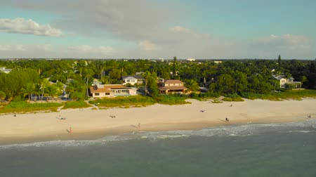 neapol : Naples, Florida is a tourist town in the USA. Drone flies along the coast over the water with a view of the coast. People walk along the ocean and enjoy the sunset. Houses by the sea, Naples, Florida.