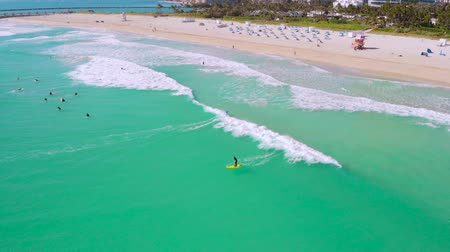 дрейф : South Pointe Beach with surfers on boards waiting for the waves from the ocean, Miami, Florida, aerial view. Miami Beach. Aerial flight Miami waves. Aerial of South Beach, Miami Beach, Florida.