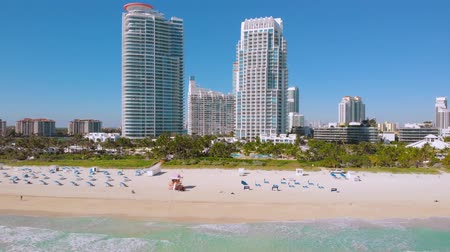 vacant : AERIAL: Flying forward to modern skyscrapers on the shore of South Pointe Beach, Miami, Florida. Aerial view flight Miami Beach waves. Downtown Miami is in the background. Miami Beach. Florida, USA Stock Footage