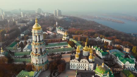 영토 : Bell tower Kiev Pechersk Lavra on evening city landscape. Aerial view architecture Kiev Pechersky Lavra in evening sunlight. Ancient orthodox architecture in Kiev city, Ukraine. Camera moves back.