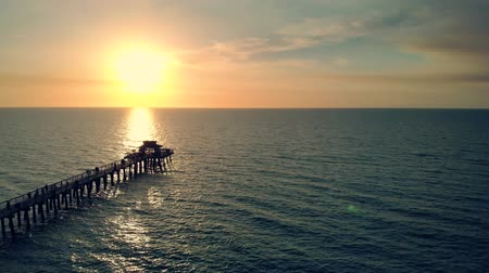 nápoles : Drone aerial of Naples coastline into the Naples fishing pier with the sunset in the background. Sunset over horizon and wooden pier of caribbean beach of Naples in Florida. Drone is flying forward. Vídeos