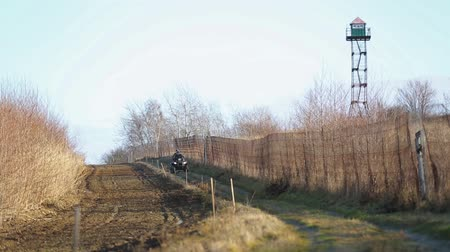 border crossing : Border guards on ATV patrols state border. State border with a fence and plowed land. Two border guards ATV. Stock Footage