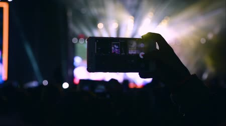 sallama : Close-up girls hands hold a smartphone and shoots video at music concert. People cheer move lift and clap their hands in unison against the strobing stage lights. Concert live video mobile phone hand