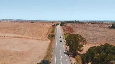 wayside : Cars drive along an asphalt desert road in a desert climate. Portugal countryside, arid climate. Bright sunny day in arid climate. Mediterranean climate Portugal