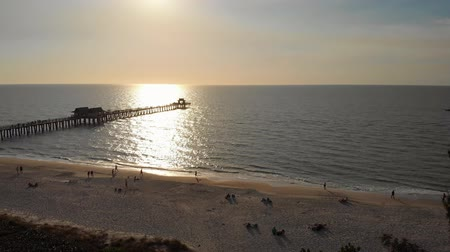 refletindo : Coast and the beach near the pier leaving into the ocean. Naples Beach Pier 4k aerial drone footage. Drone aerial of Naples coastline into the Naples fishing pier with the sunset in the background.