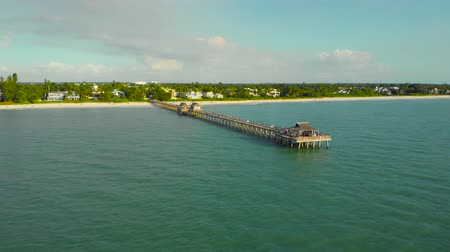 fly fishing : Drone flies around a fishing pier in Naples, Florida USA. Drone flies back, flying away from the pier. The coast and the beach near the pier leaving into the ocean. Beach near the ocean pier, aerial.