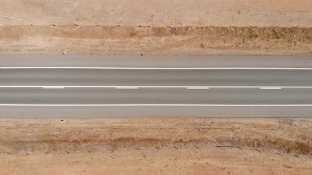 looking down : Car is standing on the sidelines on a deserted road, top view. Trucks and cars passing by a standing car, view directly from top to bottom. Desert road, view from above. Aerial top down view.
