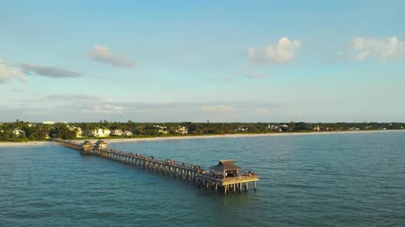 kum saati : Drone flies around a fishing pier in Naples, Florida USA. Drone aerial of the Naples Fishing Pier with sunset. Pier in Calm Ocean with High Rises in the Distance. Tourists watch sunset from the pier. Stok Video