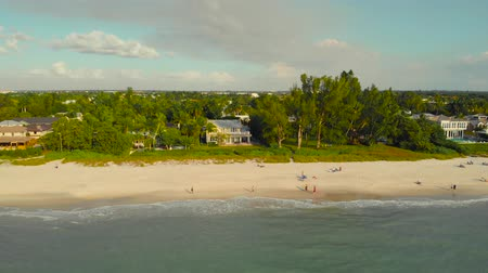 baixo : Coast and the beach near the pier leaving into the ocean. Naples, Florida is a tourist town in the USA. Drone flies along the coast over the water with a view of the coast. People walk along the ocean