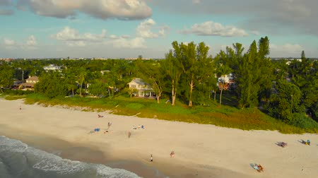 napoli : Coast and the beach near the pier leaving into the ocean. People walk along the ocean and enjoy the sunset. A drone flies along the coast over the water with a view of the coast, Naples, Florida, USA.