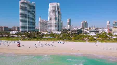 vacant : Front line with white skyscrapers and hotels near the water Miami South Beach. Surfer on a yellow logboard is floating on the azure water of the Atlantic Ocean near Miami Beach, shooting over water.