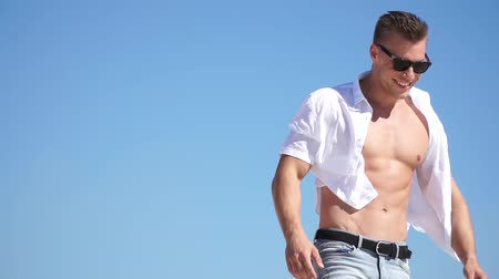 мышечный : Beautiful guy modeling appearance in a white shirt and jeans Стоковые видеозаписи