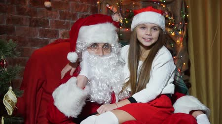posando : Closeup girl posing sitting on the hands of Santa Claus Stock Footage
