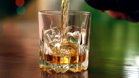 záběry :  Pouring a scotch whiskey into glass with ice