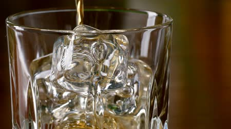 close up shot : Pouring a scotch whiskey into glass with ice.