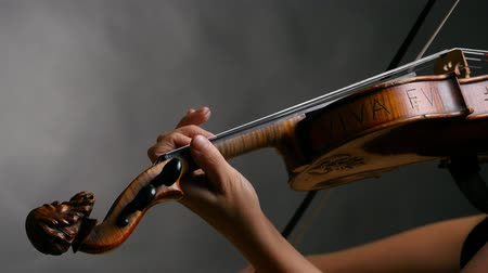 Woman playing violin over dark background.