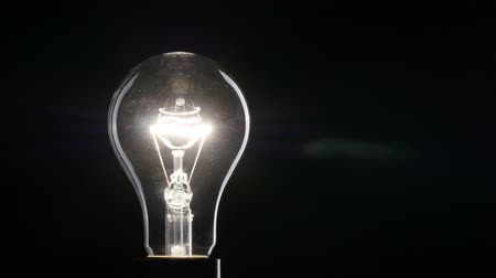 Light bulb over black background. 4K, UHD Стоковые видеозаписи