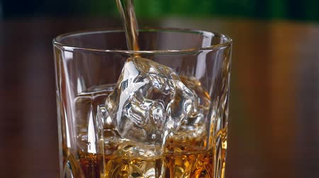 bourbon whisky : Pouring a scotch whiskey into glass with ice