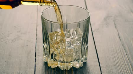 whisky : Pouring a scotch whiskey into glass with ice