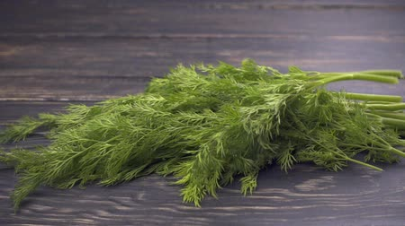 укроп : Falling dill (fennel) sprigs on wooden background. Slow motion Стоковые видеозаписи